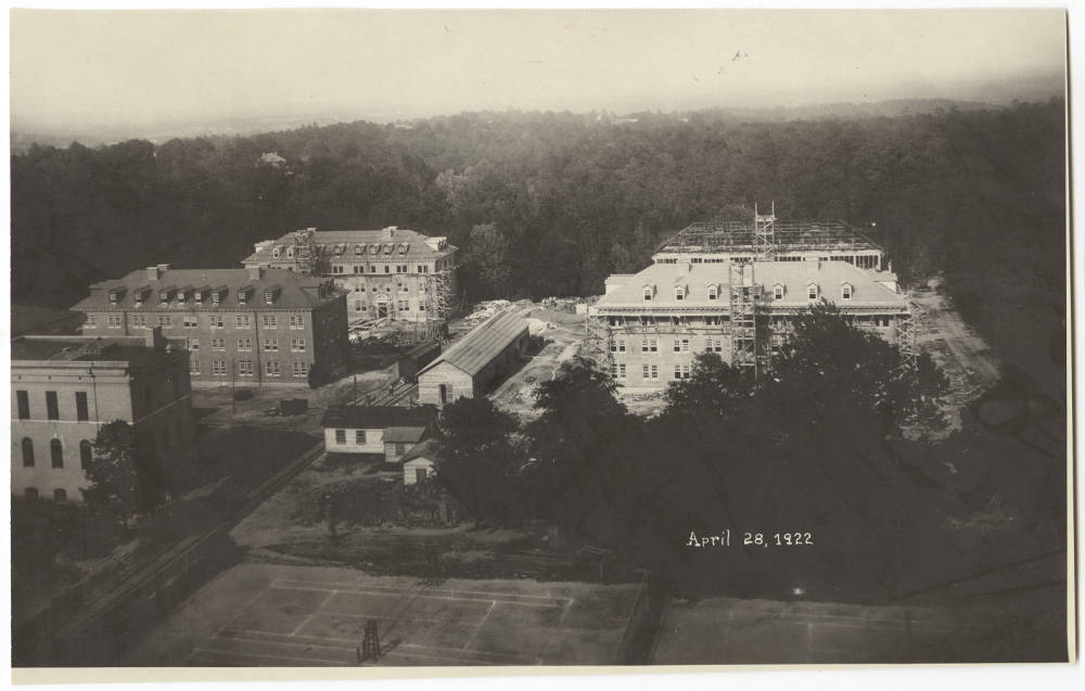 The Upper Quad dormitories under construction, April 28, 1922, showing the nearly completed Grimes (partially obscured by Caldwell Hall) at center left. The railroad spur used to transport building materials to the site can be seen running diagonally from the lower left corner. From a copy in the North Carolina Collection, Wilson Library, Chapel Hill.