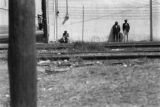 Black and White 35mm Roll Film 0500: Men leaning against building next to railroad tracks, March...