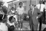 Black and White 35mm Roll Film 0702: Governor Terry Sanford walks through low income neighborhood talking to...