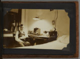 Black and White Photographic Print 0001: Paul H. Etheridge Jr. seated at desk in dorm room (#11)...